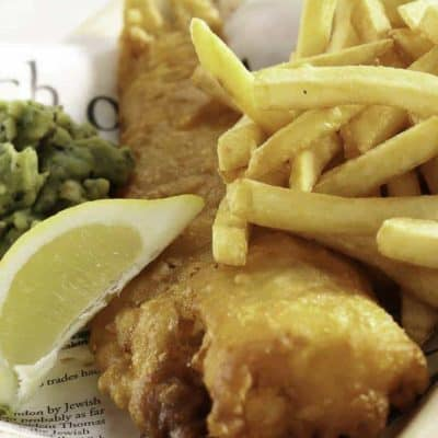 beer battered fish and chips in a basket with a slice of lemon