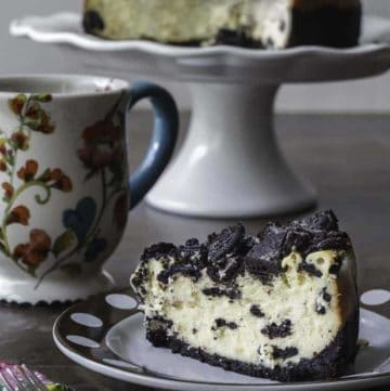 Homemade copycat Cheesecake Factory Oreo Cheesecake slice on a plate in front of cheesecake on a stand.