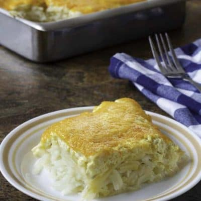 Cheesy homemade copycat Cracker Barrel hashbrown casserole on a plate and in a baking pan.
