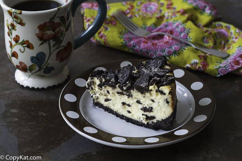 Slice of homemade copycat Cheesecake Factory Oreo Cheesecake on a plate next to a coffee mug.
