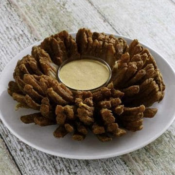 A deep fried outback steakhouse blooming onion and dipping blooming onion sauce on a plate.