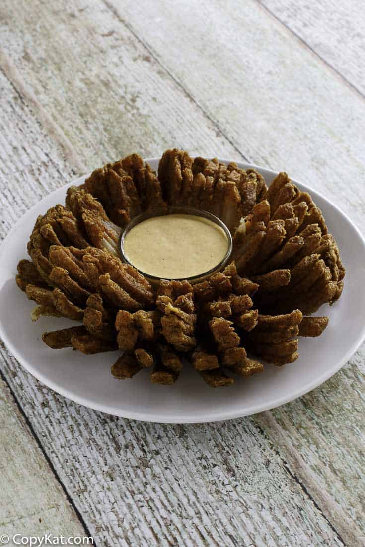 A deep-fried homemade copycat outback steakhouse bloomin onion and blooming onion dipping sauce on a plate.