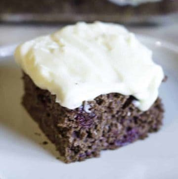 A slice of devil's food cake topped with cream cheese frosting