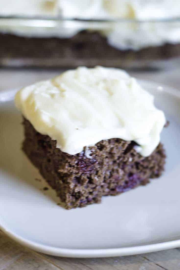 A slice of cherry devil's food cake topped with cream cheese frosting