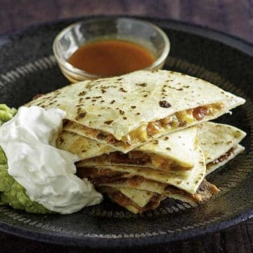 Cheese and bacon quesadilla cut into pieces served with sour cream, guacamole, and sour cream.