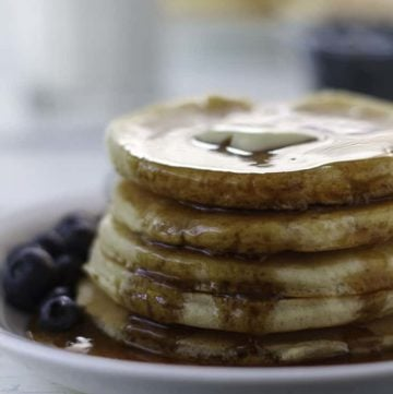 A stack of homemade copycat Ihop Buttermilk Pancakes with syrup on a plate.