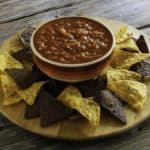 Homemade Chilis salsa in a bowl with tortilla chips around it.
