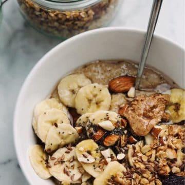 A bowl of homemade granola with sliced bananas.