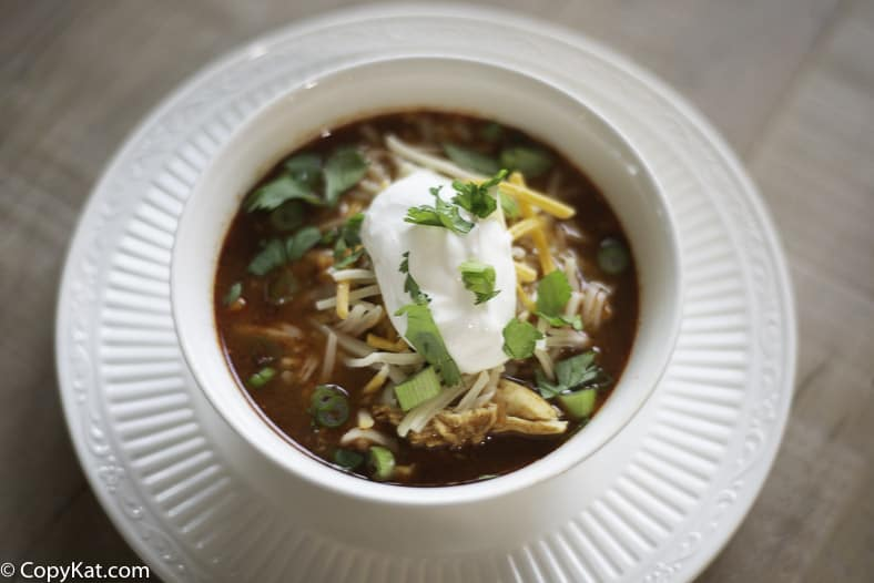 A bowl of chicken tortilla soup with sour cream and cheese on top.