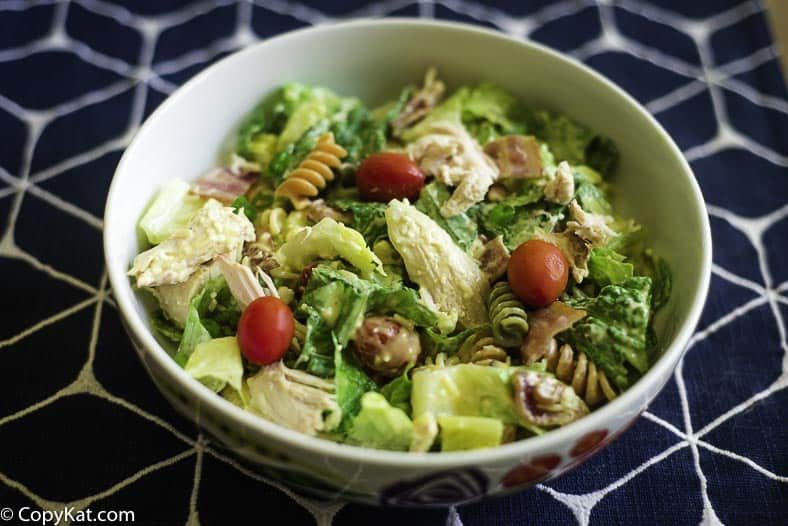 A lettuce salad with chicken, bacon, pasta, tomatoes and more.
