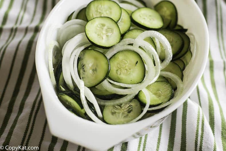 fresh sliced cucumber salad in a white dish