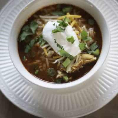 A bowl of tortilla soup with a dollop of sour cream on top