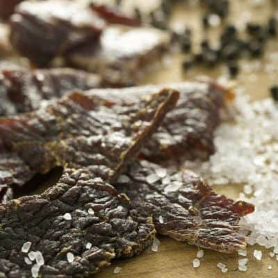 homemade spicy beef jerky on a table with spices