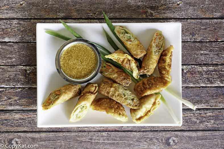 Mustard dipping sauce egg rolls on a platter