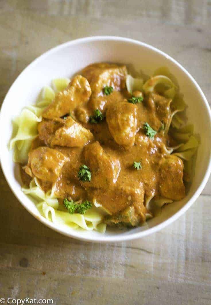 A bowl of chicken paprikash and pasta.