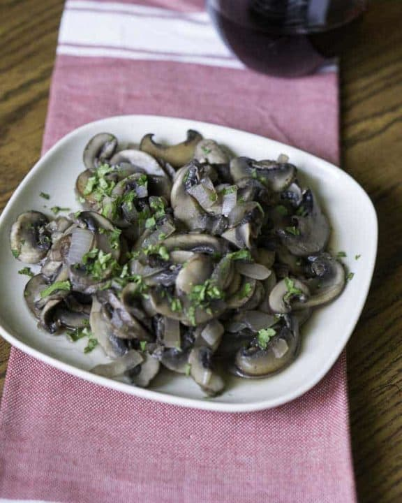 Homemade copycat Outback Steakhouse Sauteed mushrooms on a white plate on top of a red kitchen towel.