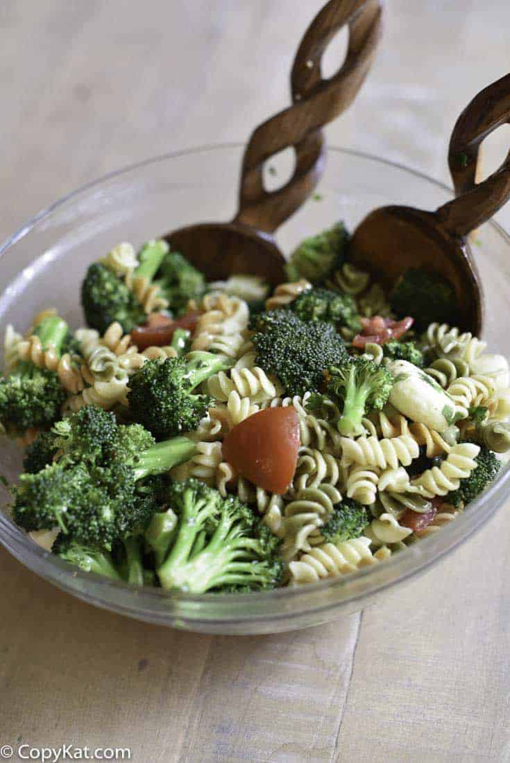 broccoli cheese pasta salad and wood salad tongs in a glass bowl