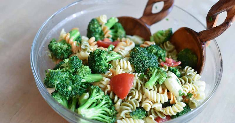 broccoli cheese pasta salad and salad tongs in a bowl