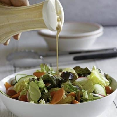 Homemade Houston's Buttermilk Ranch Salad Dressing being drizzled on a salad.
