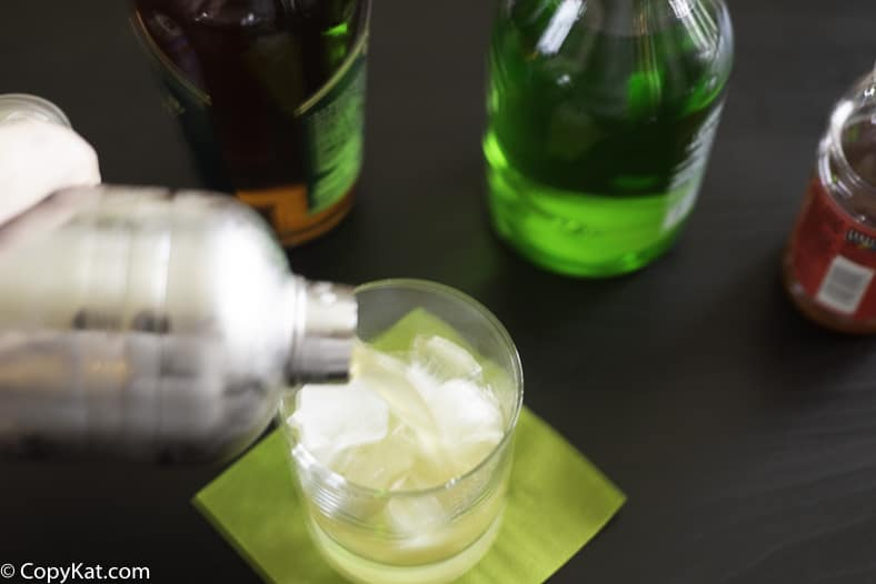 Pouring a Washington Apple cocktail into a glass from a shaker.