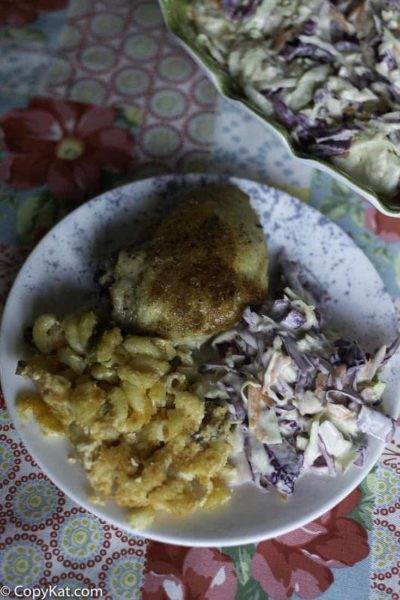 A plate with macaroni and cheese, baked chicken, and homemade coleslaw.