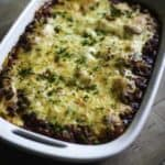 Four Cheese Manicotti with meat sauce topped with cheese in a baking dish