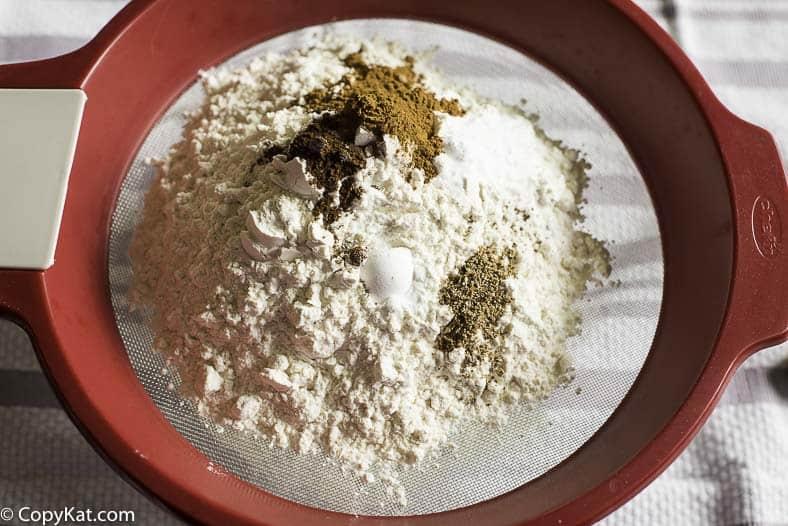 shifting flour cloves, nutmeg and cinnamon together