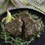 Pan seared lamb chops on a black plate.