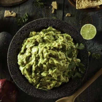 A bowl of guacamole made with fresh avocados and canned tomatoes.