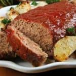 meatloaf with tomato sauce on a platter with roasted potatoes