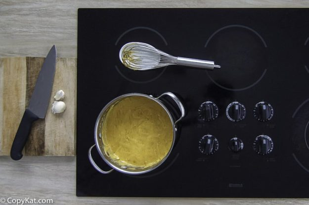Homemade copycat Melting pot Cheddar cheese fondue in a pot on the stovetop..
