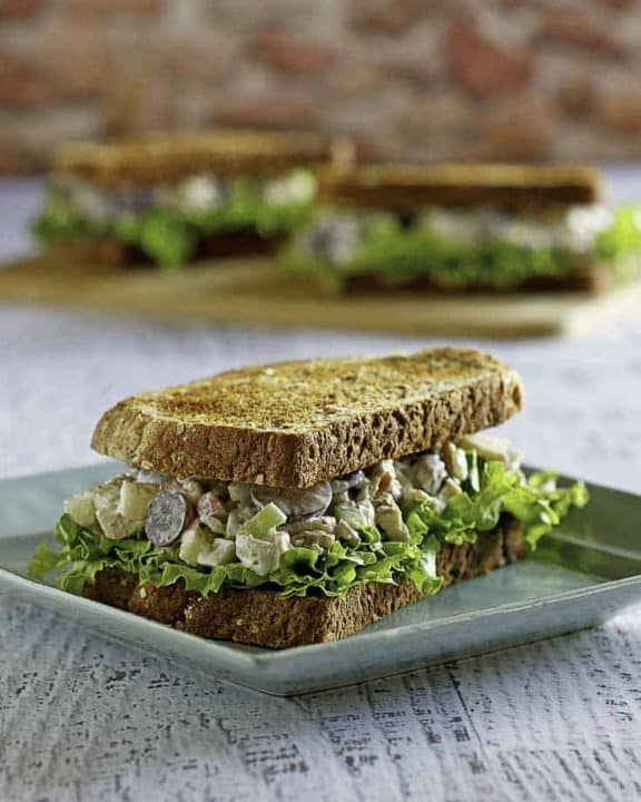Homemade copycat Arby's Grilled Chicken Pecan Salad in a sandwich on a plate.
