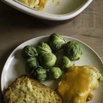 tuna stuffed crescent roll casserole on a plate with bread and Brussels sprouts