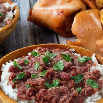 Homemade copycat Popeyes Red Beans and Rice in a bowl next to dinner rolls.