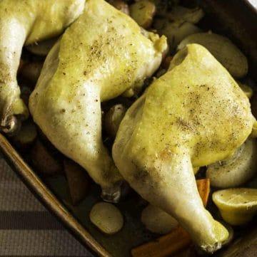 three roasted chicken leg quarts resting on root vegetables