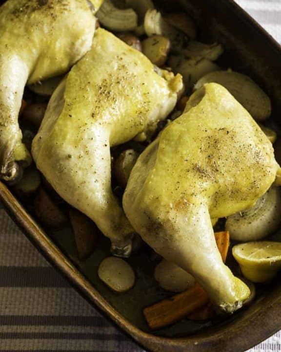 three roasted chicken leg quarts resting on root vegetables