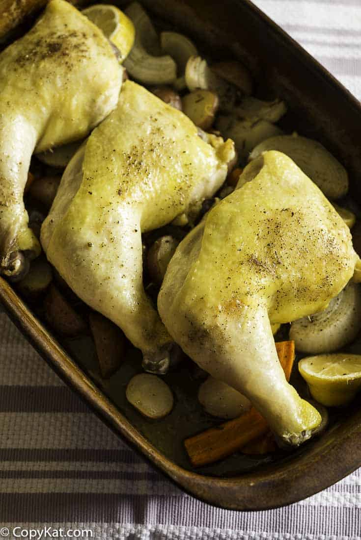 three roasted chicken leg quarter and vegetables in a roasting pan