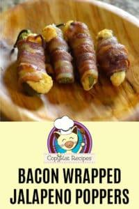 bacon wrapped jalapeno poppers on a wood plate