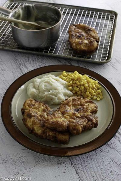 Homemade copycat Cracker Barrel Sunday Chicken, mashed potatoes, and corn on a plate.