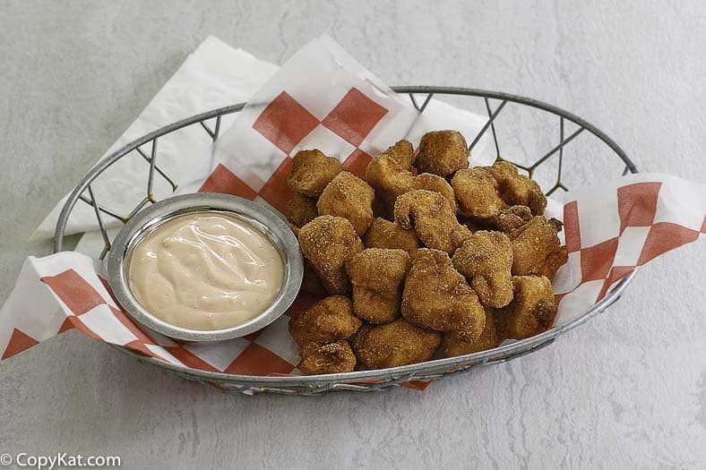 homemade chicken nuggets in a basket with a dipping sauce