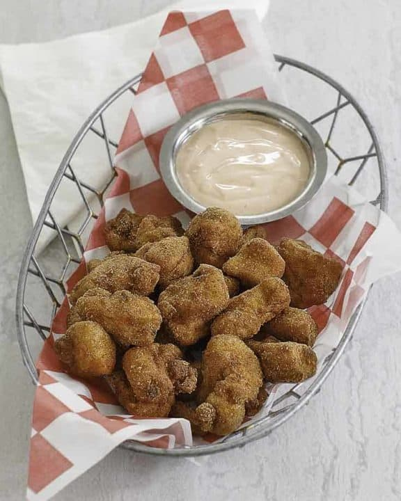 chicken nuggets and dipping sauce in a wire basket