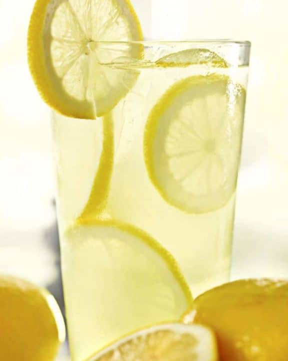 a glass of lemonade with lemon slices