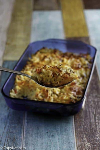 loaded hashbrown casserole on a spoon and in a baking dish