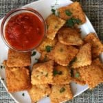 Olive Garden Toasted Ravioli and marinara sauce on a plate.