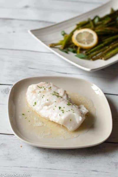 Butter Poached Monkfish on a plate next to a platter of asparagus.