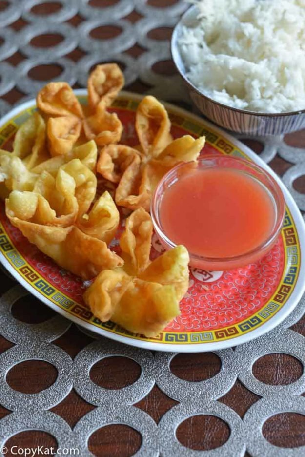 cream cheese wontons and sauce on a plate next to a bowl of rice