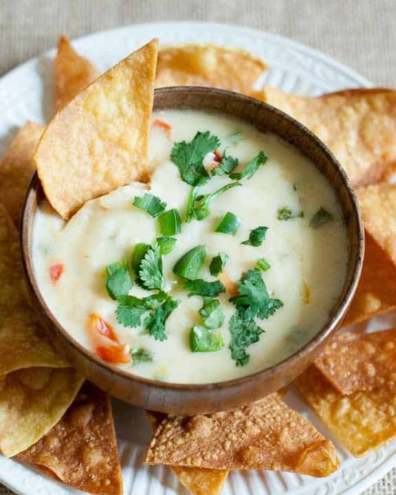 Applebees Queso Blanco dip in a bowl and tortilla chips on a platter.