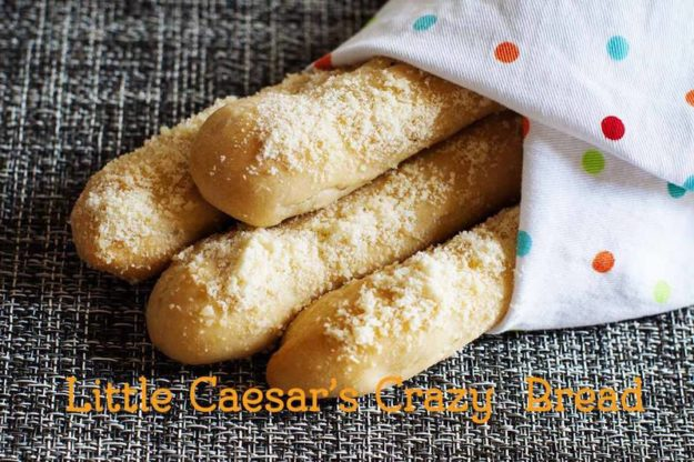 Homemade copycat Little Caesar's Crazy Bread wrapped in a kitchen towel.