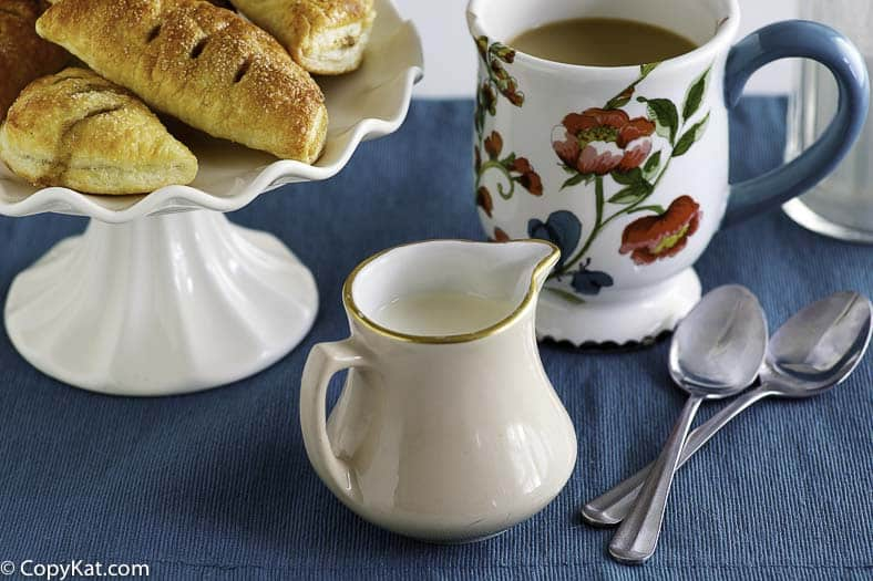 A cup of coffee made with homemade amaretto coffee creamer, and a plate of pastries.