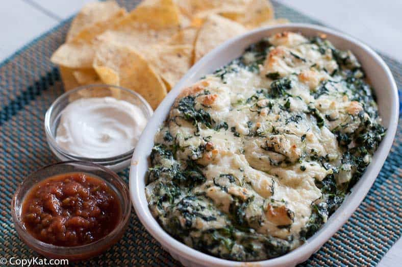 Homemade copycat Cheddars Santa Fe Spinach Dip in a white baking dish next to salsa, sour cream, and tortilla chips.